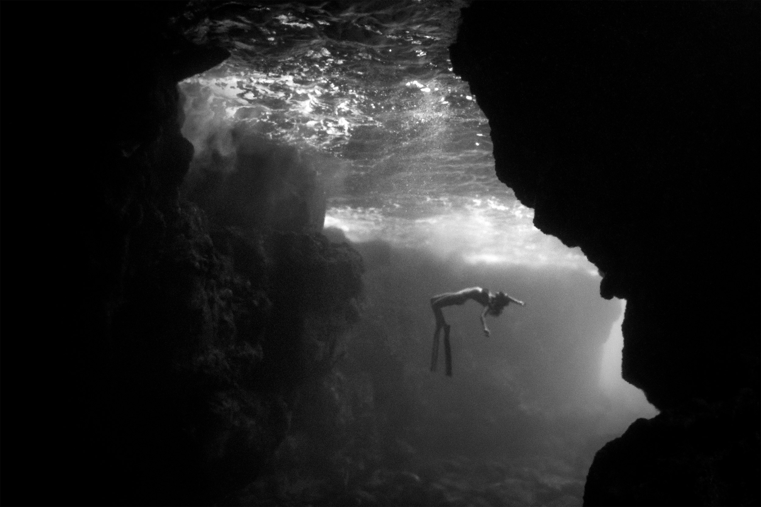 Kona - girl freediving in a cave